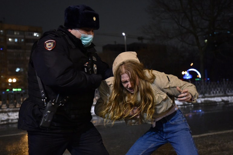A law enforcement officer detains a woman during a rally in support of jailed opposition leader Alexei Navalny in Moscow [Yuri Belyat/Reuters]