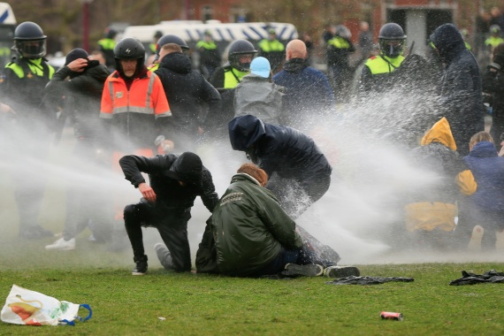 Police fire water cannon during a protest against restrictions put in place to curb the spread of the coronavirus in Amsterdam. 'This has nothing to do with protesting, this is criminal violence and that's how we'll treat it,' Rutte said. [Eva Plevier/Reuters]