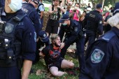 A person is arrested by police on Tuesday as protesters on Australia Day in Sydney demand that the country's national day be changed [Loren Elliott/Reuters]