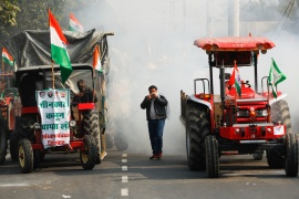 A farmer covers his face to protect himself from tear gas during the protest in New Delhi. [Adnan Abidi/Reuters]