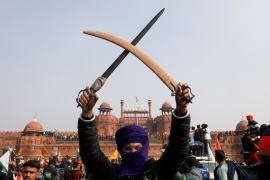 A farmer holds a sword during a protest against farm laws at the historic Red Fort in Delhi [Adnan Abidi/Reuters]