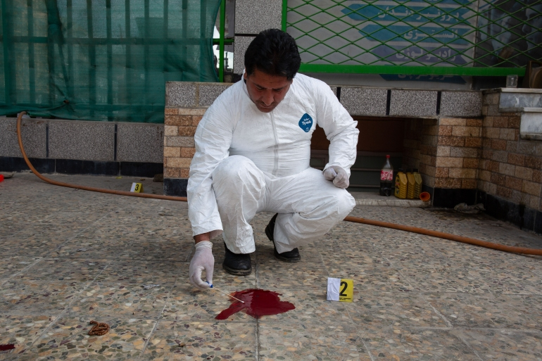 A member of the CSI team takes a sample of blood from a crime scene which will be sent to the Forensic Medicine Directorate (FMD) in Kabul for analysis [Lynzy Billing/Al Jazeera]