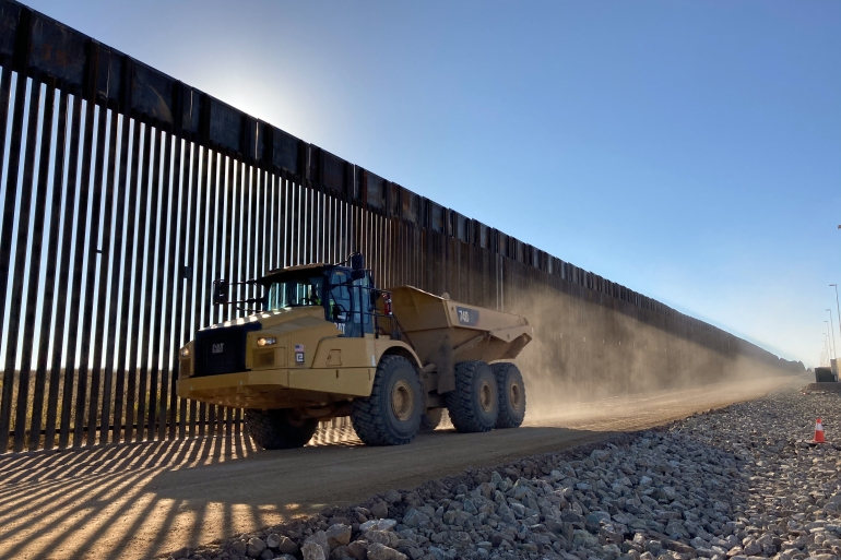 Large construction machinery blows up dust along a recently built stretch of border barrier along the San Bernardino National Wildlife Refuge in southeastern Arizona on January 8, 2021 [Megan Janetsky/Al Jazeera]