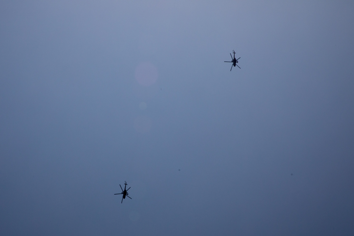 Two Russian helicopters fly over the PK12, where fighters were said to be holed up in the surrounding bushes. [Adrienne Suprenant/Al Jazeera]