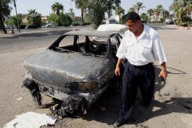 An Iraqi traffic policeman inspects a car destroyed four days ago when American Blackwater contractors opened fire on civilians, killing 17, in Nisour Square in Baghdad on September 20, 2007 [File: AP/Khalid Mohammed]