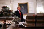 President Donald Trump ends his presidency with a litany of notable, but perhaps forgotten, moments, including the massive fast food dinner he served to college football players in 2019 [Susan Walsh/AP Photo]