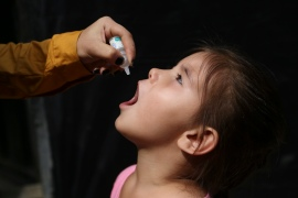 An Afghan girl is vaccinated during polio eradication campaign in Kabul [File: Mariam Zuhaib/AP]