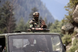 An Indian army soldier keeps guard on top of his vehicle as their convoy moves on the Srinagar- Ladakh highway [File: Mukhtar Khan/AP]
