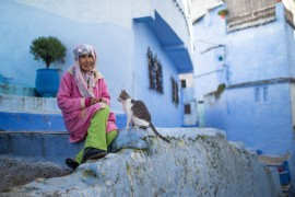 A woman sits next to her cat outside her home in an empty alleyway in Chefchaouen. [Mosa'ab Elshamy/AP Photo]
