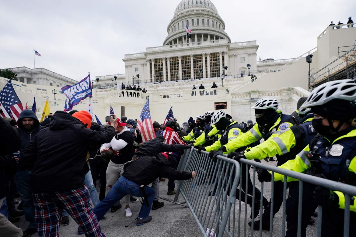 Trump supporters try to break through a police barrier at the Capitol in Washington. [Julio Cortez/AP Photo]