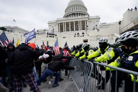 Trump supporters try to break through a police barrier at the Capitol in Washington [Julio Cortez/AP Photo]