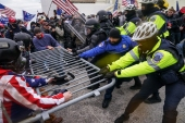 Trump supporters try to break through a police barrier, Jan 6, 2021, at the Capitol in Washington, DC [File: John Minchillo/AP Photo]