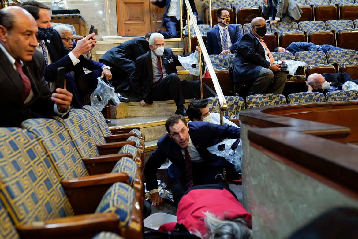 People shelter in the House gallery as protesters try to break into the Chamber of the US House of Representatives. [Andrew Harnik/AP Photo]