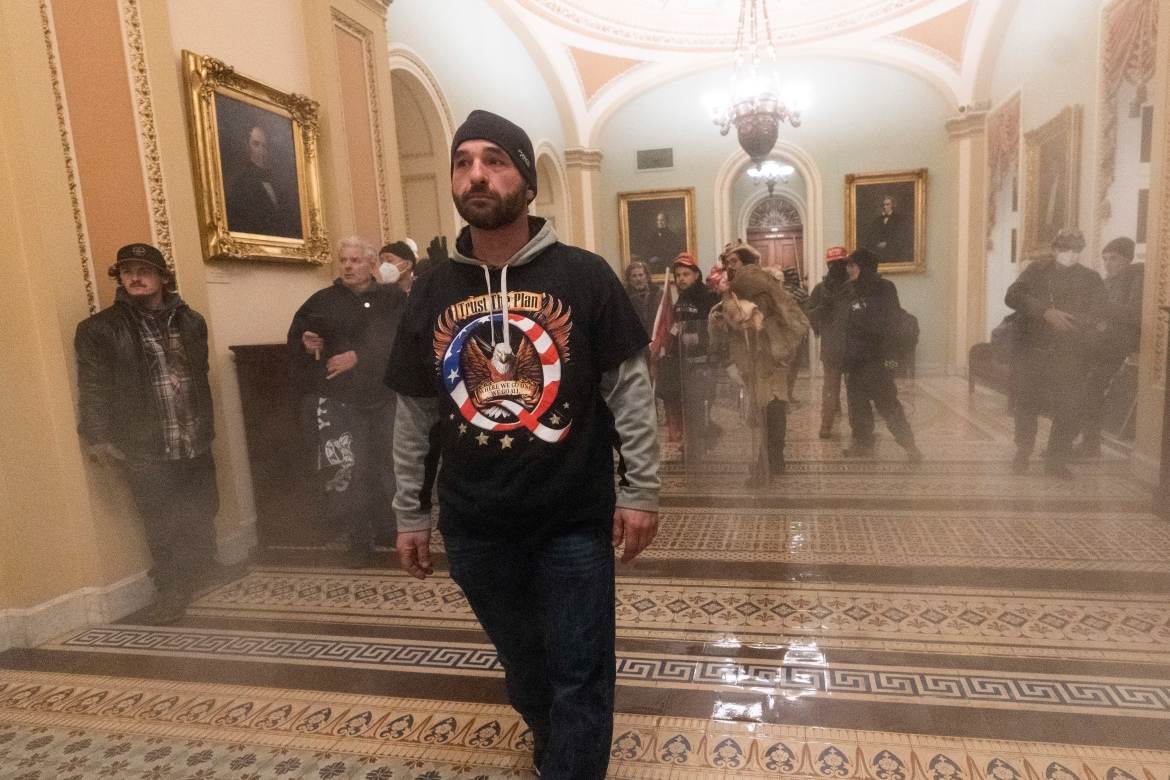 Smoke fills the walkway outside the Senate Chamber as supporters of President Donald Trump are confronted by US Capitol Police officers inside the Capitol. [Manuel Balce Ceneta/AP Photo]