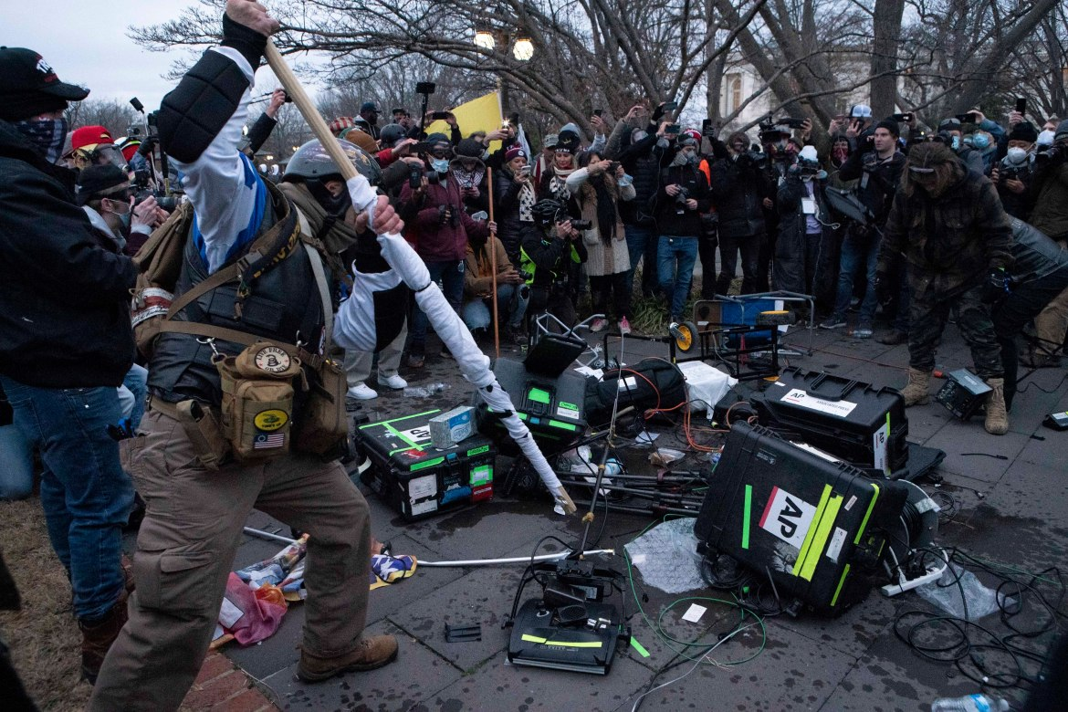 Demonstrators break TV equipment outside the US Capitol. [Jose Luis Magana/AP Photo]