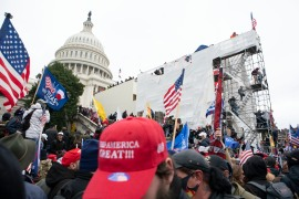 Supporters of President Donald Trump climb on an inauguration platform on the West Front of the United States Capitol on January 6, 2021 [Jose Luis Magana/AP Photo]