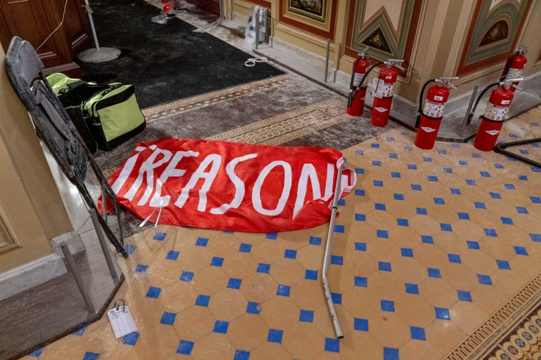 A flag that reads 'treason' is visible on the ground after protesters stormed the United States Capitol in Washington, DC [Andrew Harnik/AP Photo]