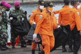 Rescuers carry body bags with human remains recovered from the sea where a Sriwijaya Air passenger jet went down [Tatan Syuflana/AP Photo]