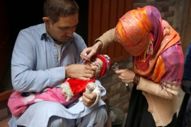 A healthcare worker administers a polio vaccine to a child in Lahore [KM Chaudary/AP]