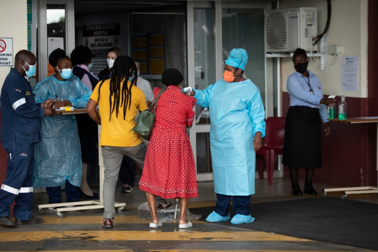 A health worker checks the temperature of an elderly patient at the emergency entrance of the Steve Biko Academic Hospital in Pretoria, South Africa on January 11, 2021 [Themba Hadebe/AP Photo]