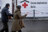 Two persons arrive at a new coronavirus, COVID-19, vaccination center in German [AP]
