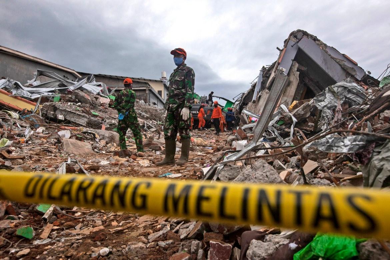 Tim penyelamat mencari korban di reruntuhan bangunan yang rata saat gempa.  [Yusuf Wahil / Foto AP]