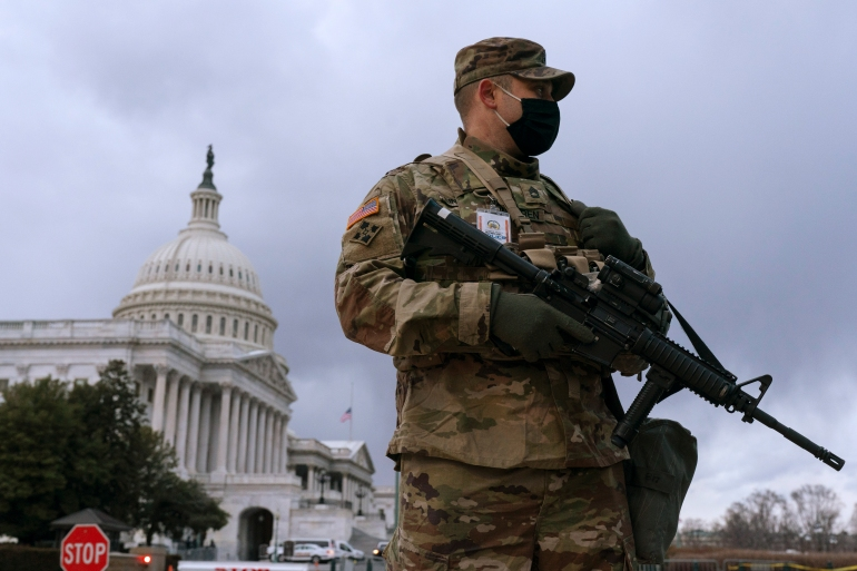 With the US Capitol in the background, a member of the Virginia National Guard stands at the ready inside the secured Capitol complex, on Saturday, January 16, 2021, in Washington, as security is increased ahead of the inauguration of President-elect Joe Biden and Vice President-elect Kamala Harris [Jacquelyn Martin/ AP]