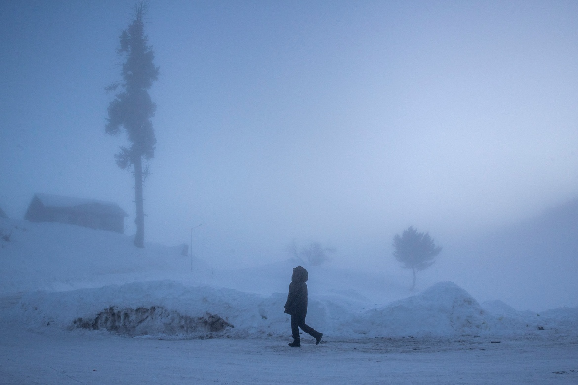 A tourist enjoys the morning walk on a snow-covered road in Gulmarg. [Dar Yasin/AP Photo]