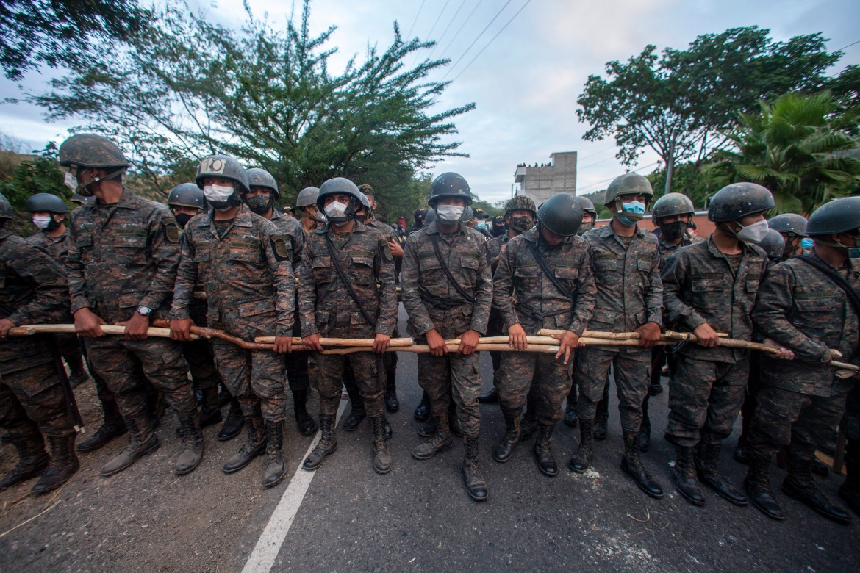 Guatemalan soldiers block part of a Honduran migrant caravan in Vado Hondo, hoping to block the caravan's progress to the US border. [Sandra Sebastian/AP Photo]