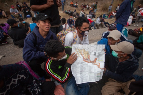 Honduran migrants show their route on a map of Mexico and Central America, as they sit near a police roadblock. [Sandra Sebastian/AP Photo]