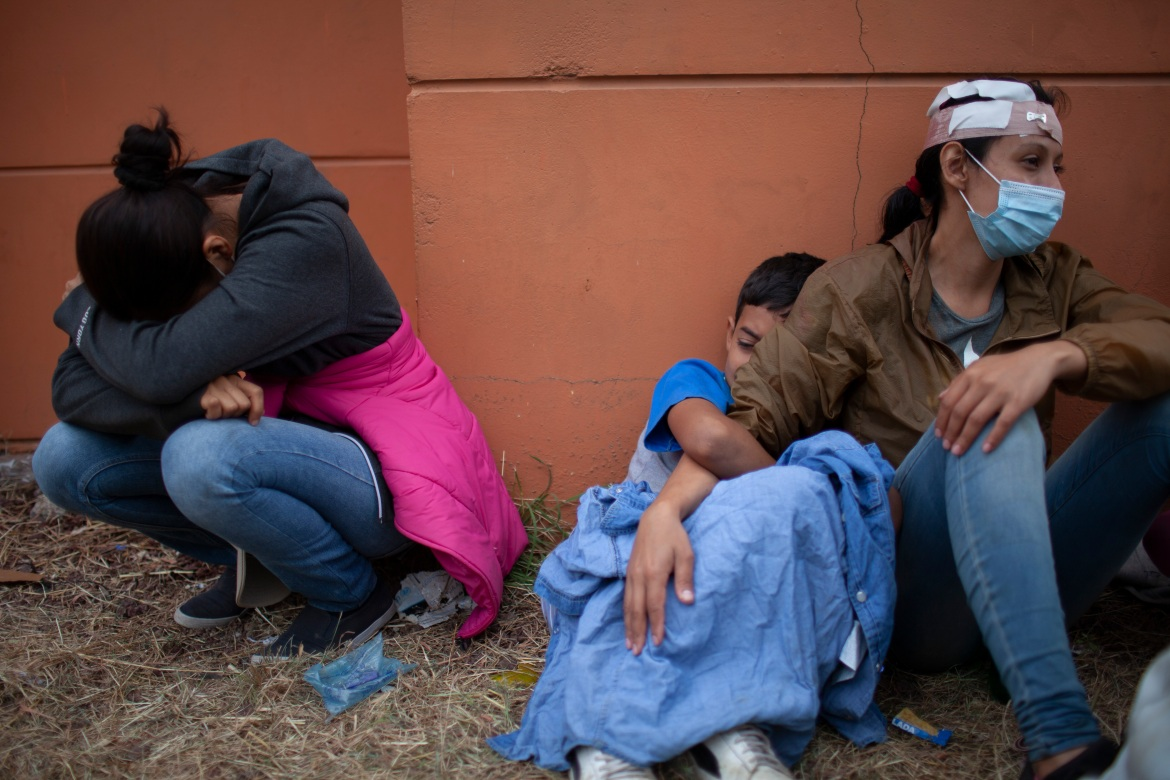 Injured female members of the Honduran migrant caravan sit on the side of a highway after being turned back by Guatemalan security forces. [Sandra Sebastian/AP Photo]