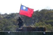 A soldier holds a Taiwan national flag during a military exercise in Hsinchu County, northern Taiwan, on January 19, 2021 [Chiang Ying-ying/ AP]