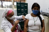 A Tenonde Pora Indigenous woman gets a shot of China's Sinovac CoronaVac vaccine for COVID-19 on the outskirts of Sao Paulo, Brazil [Marcelo Chello/Reuters]