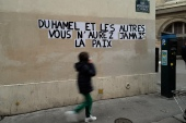 A sign on a Parisian wall reads 'Duhamel, and the others, you will never be in peace', referring to the prominent French political expert Olivier Duhamel, who is accused of raping his stepson [Francois Mori/AP]