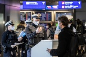 Officers check passengers arriving by plane from Prague at the Frankfurt Airport, Germany [Boris Roessler/DPA/AP Photo]
