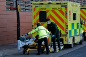 A patient is pushed from an ambulance outside the Royal London Hospital in east London [Matt Dunham/AP]