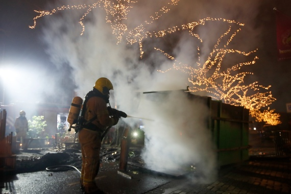 A firefighter extinguishes a container that was set alight during protests against a nationwide curfew in Rotterdam. [Peter Dejong/AP Photo]