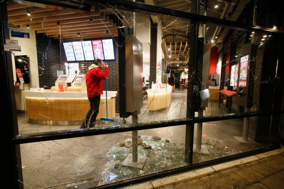 A man cleans up broken glass from smashed windows in a fast-food restaurant that was damaged in rioting in Rotterdam. [Peter Dejong/AP Photo]