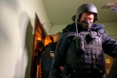 Police walk out from a door of the apartment where Oleg Navalny lives, brother of jailed opposition leader Alexey Navalny, in Moscow, Russia, Wednesday, January 27, 2021. [Mstyslav Chernov/AP Photo]
