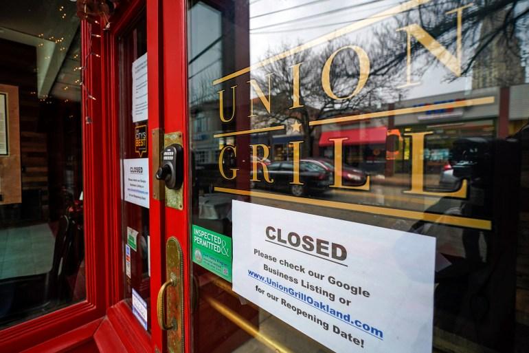 Sebuah tanda tergantung di pintu restoran Union Grill, ditutup sementara karena COVID-19, di lingkungan Oakland di Pittsburgh, Pennsylvania, Amerika Serikat [File: Gene J Puskar]