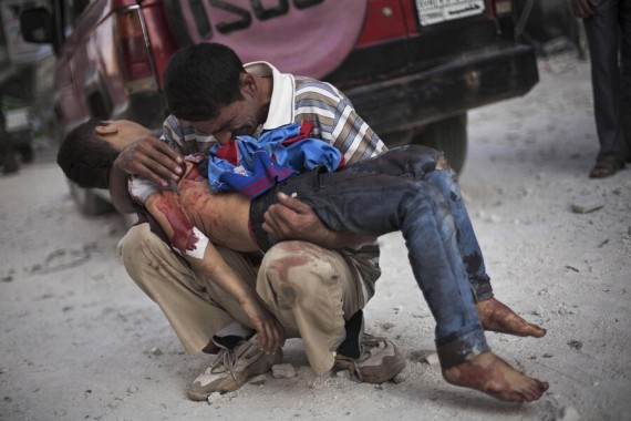 A Syrian man cries while holding the body of his son near Dar Al Shifa Hospital in Aleppo. The boy was killed by the Syrian army [File: Manu Brabo/AP Photo]