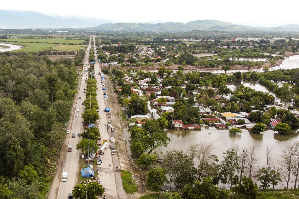 Displaced families are camping next to the highway between San Pedro Sula and La Lima. To the right, many of their homes and fields remain flooded several weeks after the storms. [Christian Jepsen/NRC]