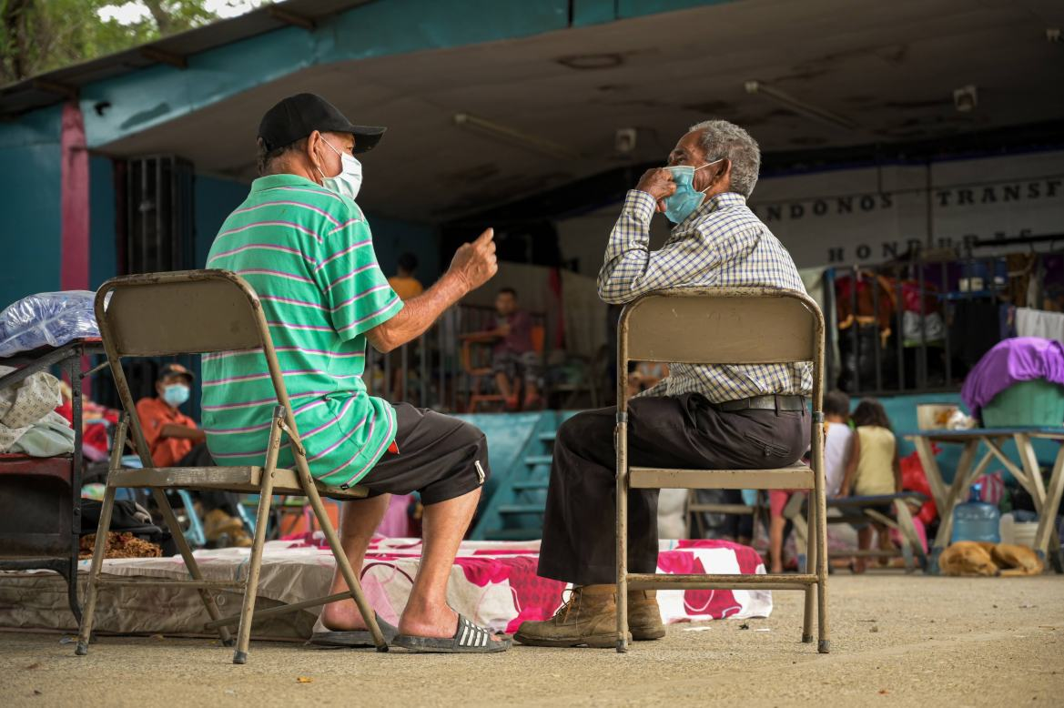 Two men having a quiet discussion in Alta Gracia Sanchez School, where they now live after their homes were flooded during tropical storms Eta and Iota. [Christian Jepsen/NRC]
