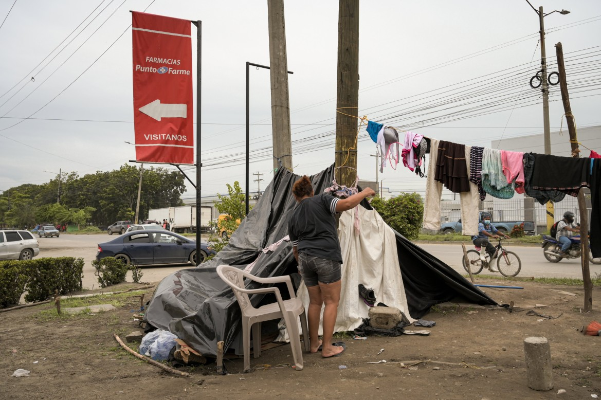 After the floods, displaced families have constructed makeshift shelters of plastic, rope and sticks along the highway between San Pedro and La Lima. [Christian Jepsen/NRC]