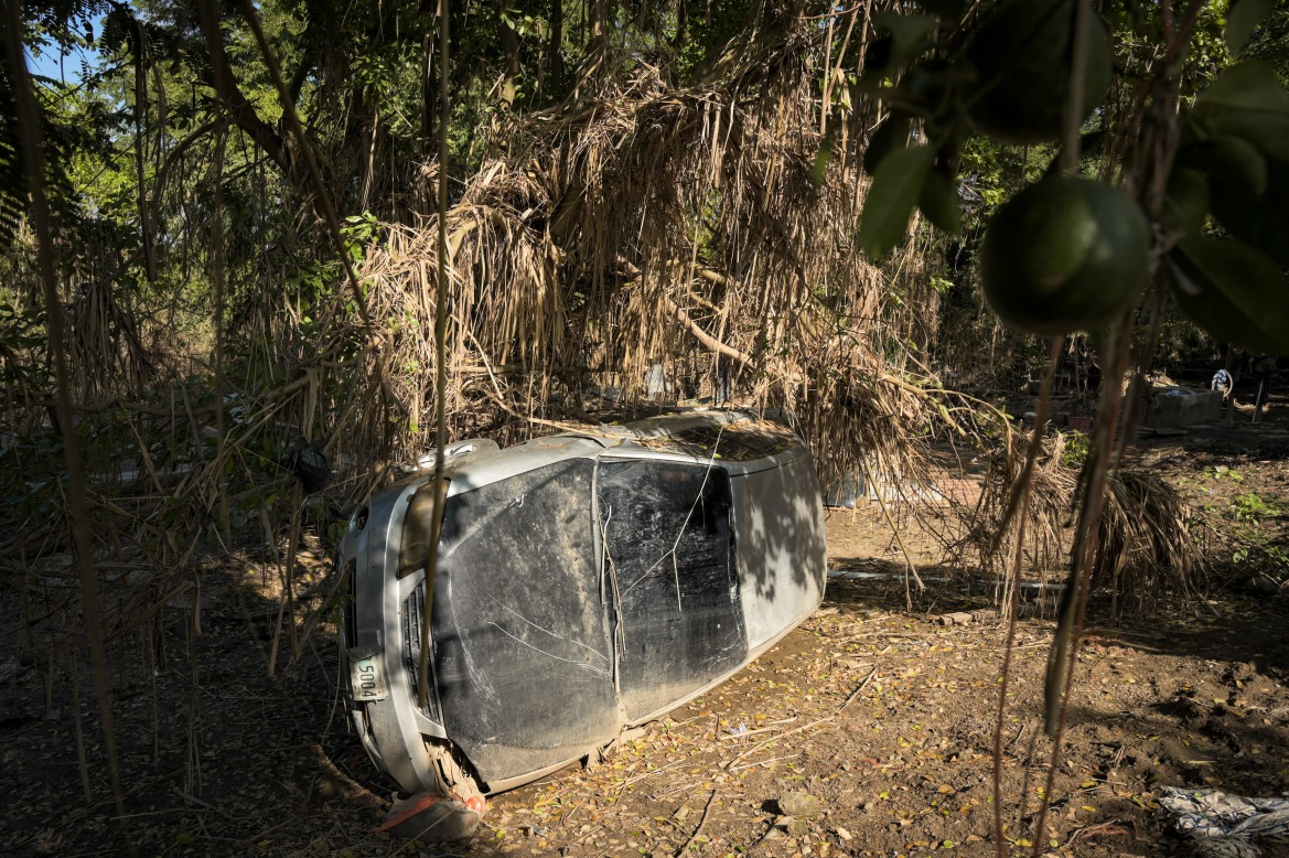A car turned over by mudslides in Cruz de Valencia village, where residents say many people were swept away by the floodwaters and had to grab trees to rescue themselves from drowning. [Christian Jepsen/NRC]
