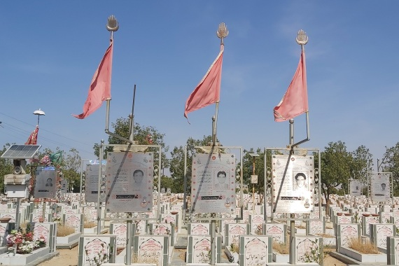 Red flags on the graves indicate the person was killed for being a Shia [Sana Batool/Al Jazeera]