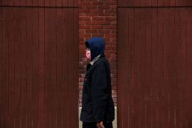 A man walks with a protective face mask in Cleveland, Ohio, which was one part of the United States that reported a loss in momentum in its economic recovery due to a rise in coronavirus infections [File: Shannon Stapleton/Reuters]