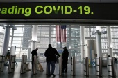 COVID-19 information is displayed on a screen as people walk around South Ferry Station in New York, on January 5 [File: Eduardo Munoz/Reuters]