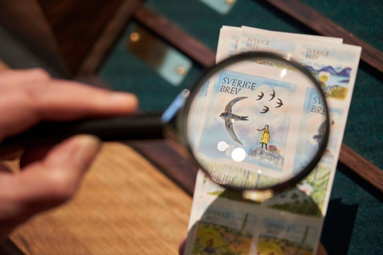The Greta Thunberg postal stamp, part of a series focusing on the environment, is seen through a magnifying glass in Stockholm [File: David Keyton/AP Photo]