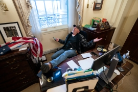 Richard Barnett sits on the desk of US House Speaker Nancy Pelosi, after supporters of former US President Donald Trump breached the US Capitol on January 6, 2021 [File: Jim Lo Scalzo/EPA-EFE]
